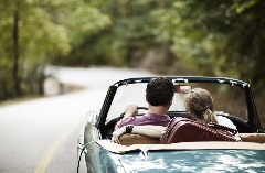 Couple riding in a blue convertible down a country road