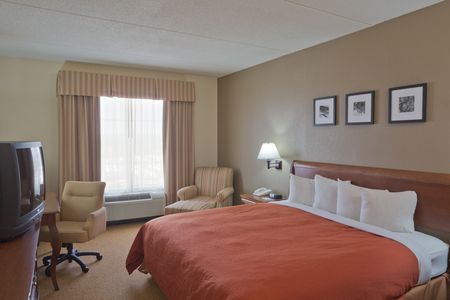 Hotel room near BWI airport with a TV, a king bed and a chair