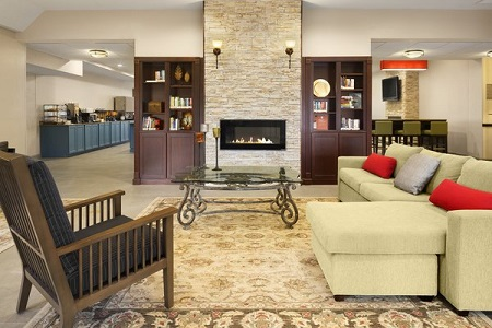Inviting hotel lobby features sofa, fireplace and subtle art pieces