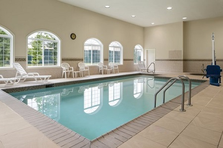 Indoor pool and hot tub area with white chairs