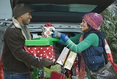 Man and woman dressed festively unloading Christmas packages