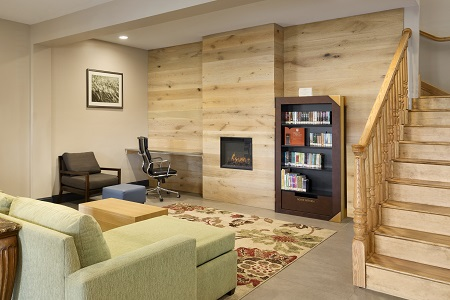 Welcoming lobby with a fireplace, a bookshelf and a patterned rug