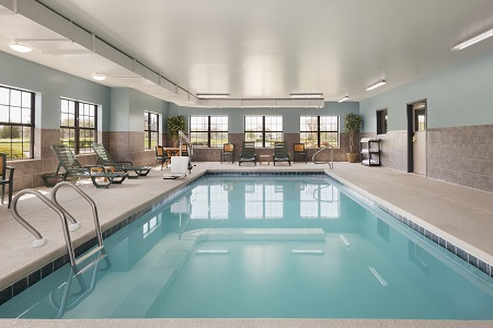 Sparkling indoor pool surrounded by green lounge chairs
