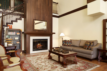 Hotel's lobby with fireplace, couch and open staircase