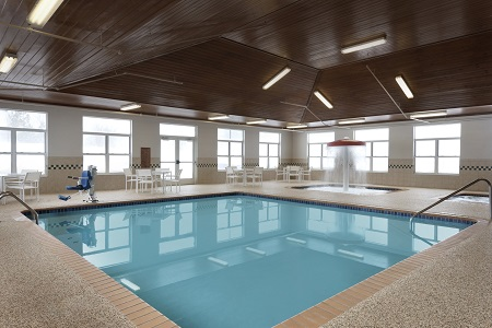 Indoor pool with poolside tables and chairs