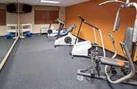 Fitness center with cardio machines and an orange accent wall