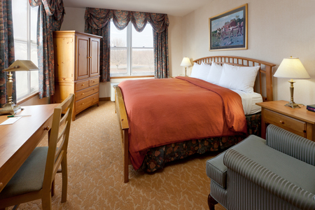 Hotel room with a king bed and light wood furniture