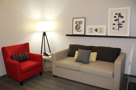 Hotel suite living room with a sleeper sofa and red armchair