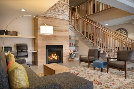Welcoming lobby with a gray sectional, two armchairs and a modern fireplace