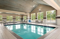 Indoor pool area with a high ceiling and large windows