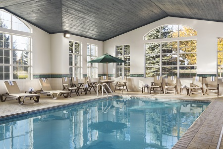 Hotel's indoor pool with seating and tables