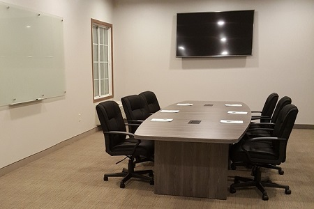 Meeting room with a conference table, flat-screen TV and whiteboard