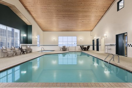 Indoor pool with seating and a hot tub