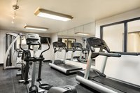 Well-lit fitness center with cardio equipment