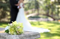 Wedding bouquet with couple in background