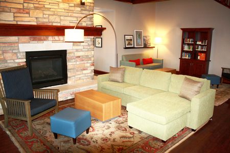 Red Wing hotel lobby with a green sectional and a welcoming fireplace