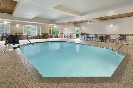Indoor pool area with green patio furniture