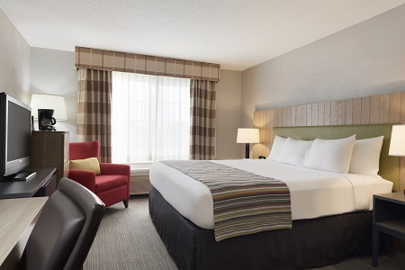 Shakopee hotel room with king bed, chair and work desk