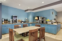 Breakfast area with tables, chairs, blue walls and blue cabinets