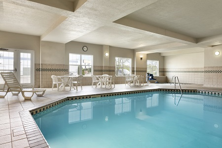 Indoor pool area with white lounge chairs and patio furniture