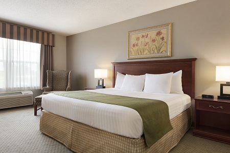Crisp, white linens on a king-size bed at our St. Cloud hotel