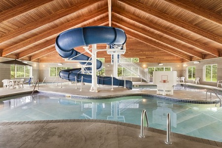 Indoor pool with waterslide and basketball hoop