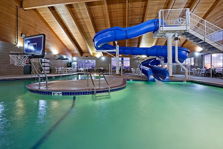 Indoor pool with waterslide and basketball goal