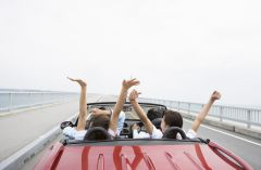 Friends enjoying a road trip in a red convertible