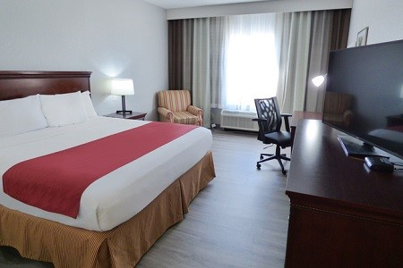 Hotel room with a king bed, striped armchair and flat-screen TV