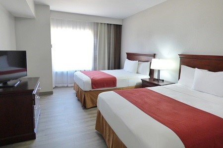 Guest room featuring a flat-screen TV and two queen beds with red bed runners