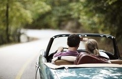 A man and woman in a blue convertible driving down the road