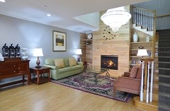 Lobby sitting area with a fireplace, a green sofa and a coffee station