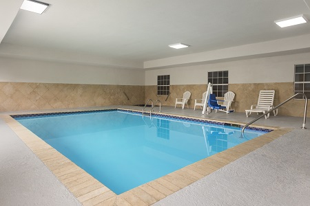 Indoor pool with white chairs
