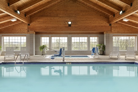 Heated indoor pool surrounded by lounge chairs