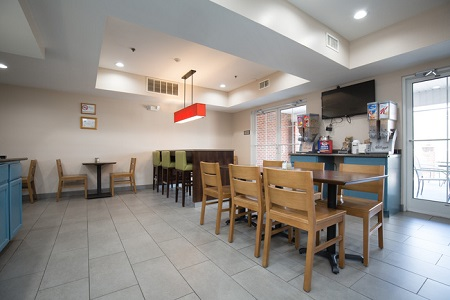 Dining area with tables, chairs, bar stools, a flat-screen TV, and hot and cold cereals