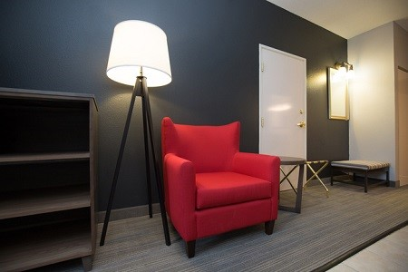 Suite living room with a lamp, red armchair and dark blue accent wall