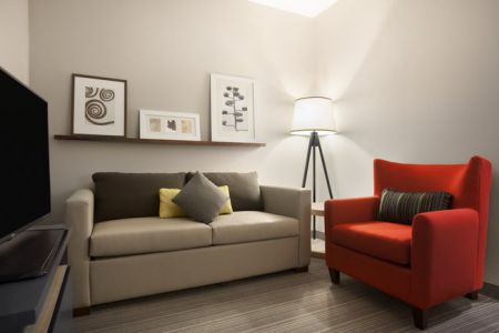 Suite living room with a flat-screen TV, sofa and red armchair