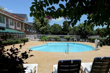 Our Charlotte hotel's sparkling outdoor pool with lounge chairs