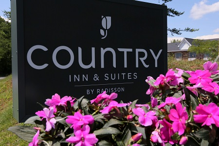 Hotel exterior sign surrounded by flowers