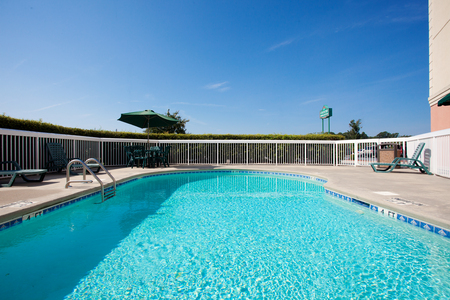 Outdoor pool surrounded by a white fence and green chairs