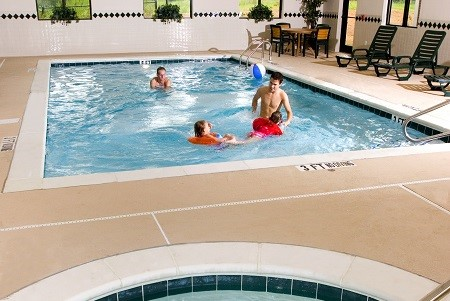 Family playing in the indoor pool beside the hot tub