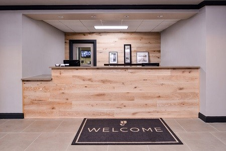 Reception area featuring a welcome mat and front desk with wood accents