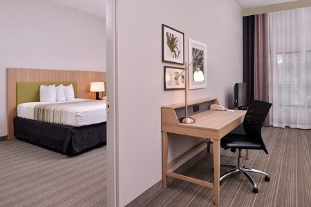 Hotel suite with a private bedroom, a work desk and a flat-screen TV
