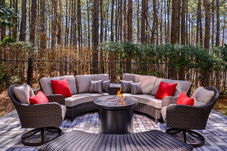 Modern fire pit surrounded by wicker patio furniture with plush cushions