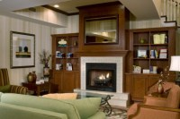 Hotel lobby's fireplace flanked by dark wood bookshelves