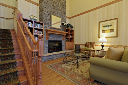 Lobby with stone fireplace and wooden staircase