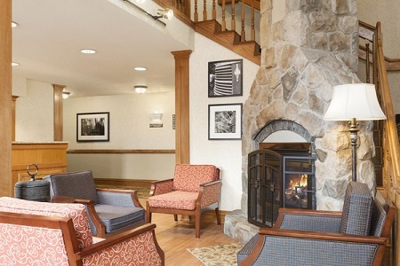 Hotel lobby with a stone fireplace and patterned armchairs
