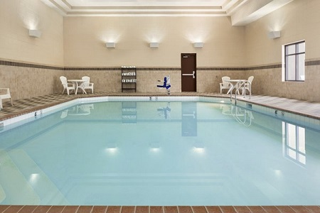 Heated indoor pool surrounded by white deck chairs
