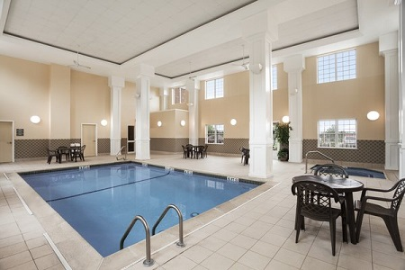 Indoor pool with white columns and seating areas
