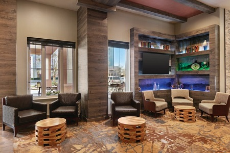 Hotel lobby with armchairs, modern accents and a mounted flat-screen TV